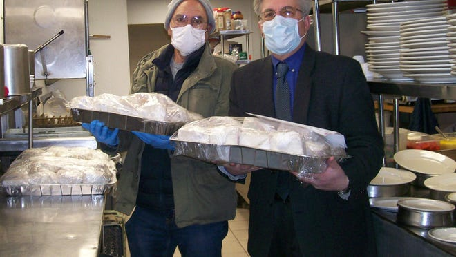 From left, Kiwanis Board Member Jeff Siegel and  Kiwanis VP Rob Green carrying trays of sandwiches from Tilly's Diner to transport to CRMC.