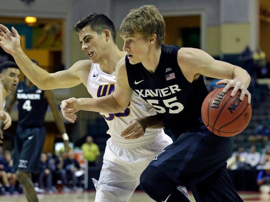 Xavier's J.P. Macura, right, drives around Northern