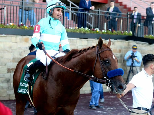 Martin Garcia, top, and Charlatan head into the Winner's Circle after winning the first division of the Arkansas Derby horse race Saturday, May 2, 2020, at Oaklawn Racing Casino Resort in Hot Springs, Ark. (Richard Rasmussen/The Sentinel-Record via AP)