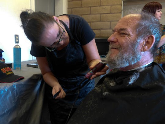 Ralph Sanders, a U.S. Marine Corps veteran, gets a trim Thursday at the North Valley Stand Down.
