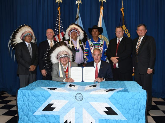 In this photo provided by the Department of the Interior Blackfeet Tribal Chairman Harry Barnes, front left, sits with U.S. Interior Sec. Ryan Zinke, front right, while posing for a photograph with members of Montana's congressional delegation and Blackfeet leaders after signing a water agreement for the tribe at the Department of Interior, Tuesday, June 12, 2018, in Washington, D.C. The agreement calls for improvements to irrigation systems, the development of a community water system and land acquisition.  (Tami Heilemann/Department of the Interior via AP)