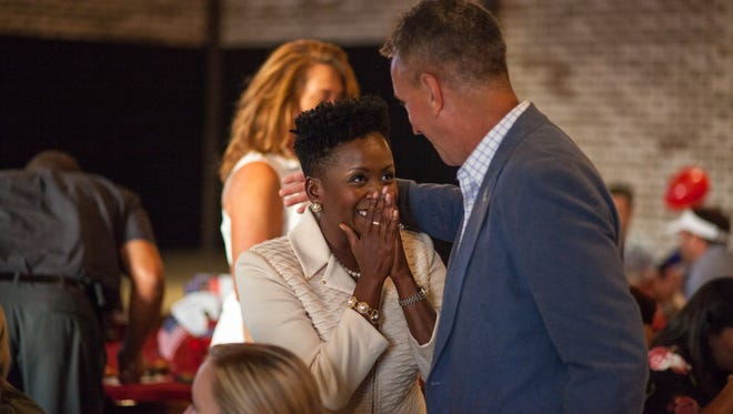 Independent candidate for County Trustee Kimberly Wiggins, center, celebrates after with supporter Rich Holladay after seeing her 10 percetage point lead at The Belle Hollow when early votes were tallied on Thursday.