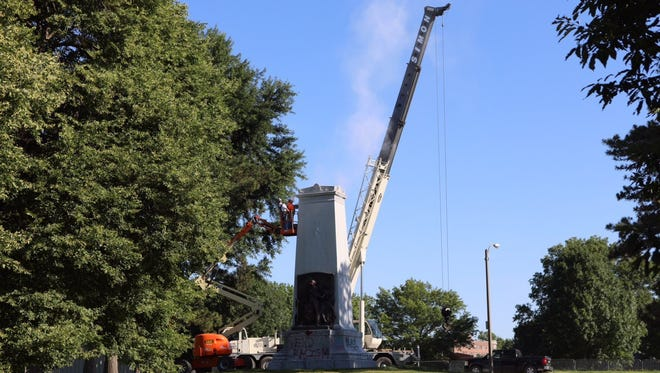 Workers at the Confederate Monument in Forest Park on Thursday, June 8, 2017. A portion of a 38-foot-tall granite monument to the Confederacy in St. Louis has been removed, but a spokesman for the mayor's office says the bulk of the memorial may remain in place for weeks.