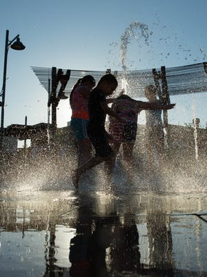 Kids play in the splash pad during the first evening farmers market at the year at the Plaza de Las Cruces, Wednesday, June 14, 2017.