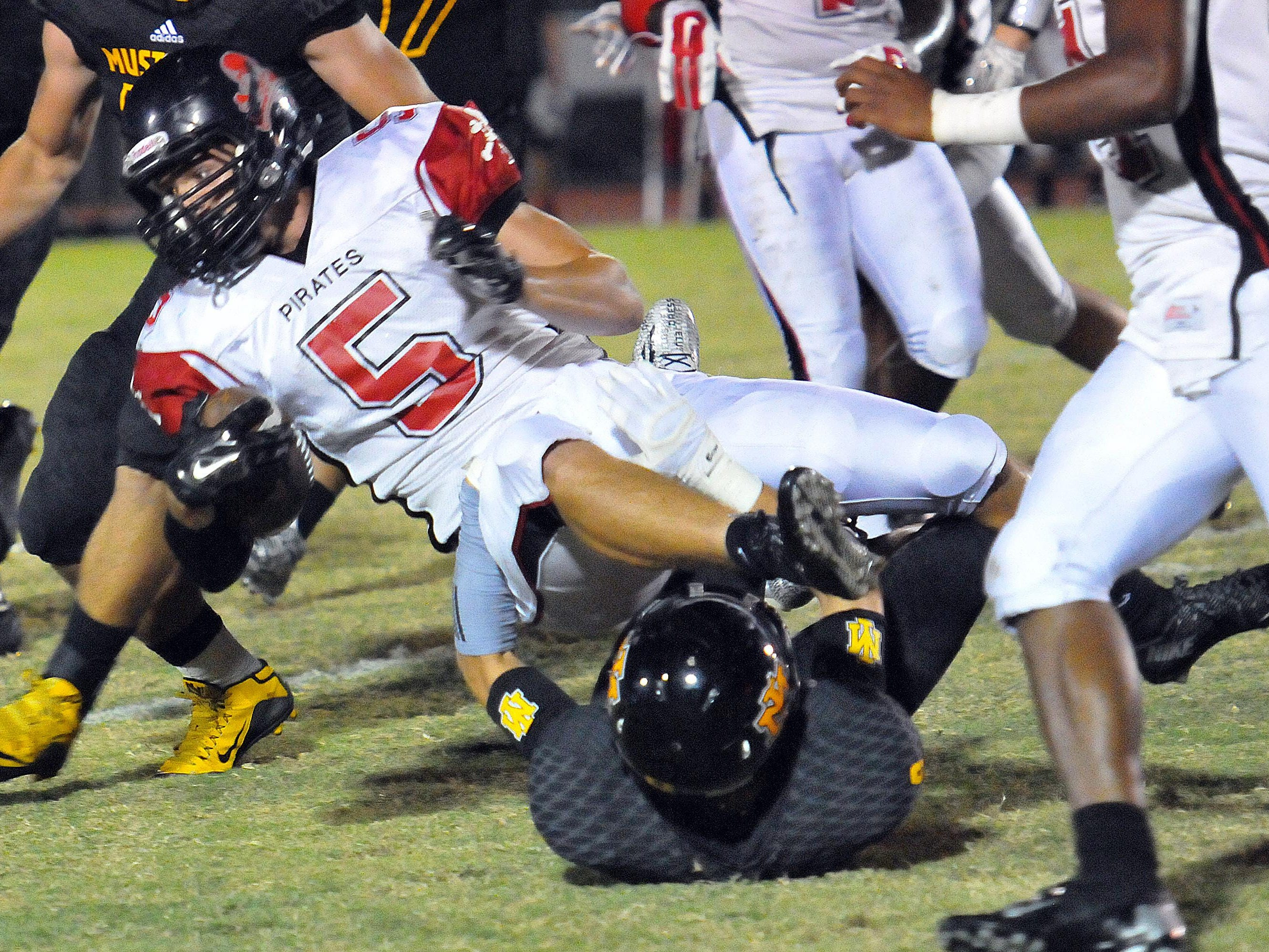 Palm Bay High's Jared Morris dives for extra yards over Merritt Island defenders.