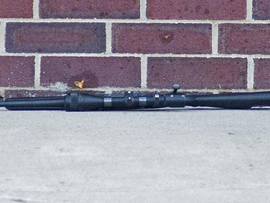 A Remington Model 700 rifle rests near the body of a DCF worker shot and killed outside Barre City Place Friday night.
