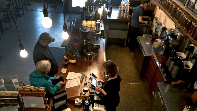 Employee Maleva Butkiewicz and general manager Nicholas Loukidis, top right, work behind the counter at Lou's Brews Cafe on Friday in Appleton.