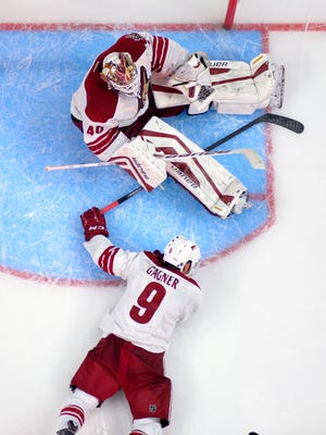 Arizona Coyotes goalie Devan Dubnyk, top, sits on the ice along with center Sam Gagner after Dubnyk was scored on by Los Angeles Kings center Trevor Lewis during the third period on Saturday, Dec. 20, 2014, in Los Angeles.