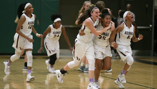 Aquinas' Kayla Jackson (35) celebrates with Erica Knapp (11) and Chanel Alexander (5) after winning the Class A2 title beating Honeoye Fall-Lima 57-52.