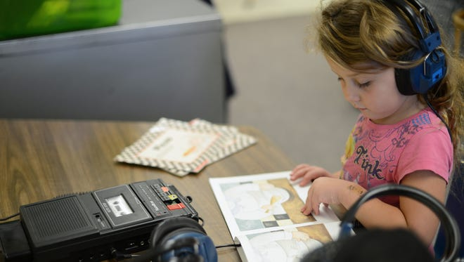 Carli Hoskins listens to an audio recording and follows along in a book about making pizza in Linda Riebe's kindergarten class at Keller Elementary School in Green Bay.