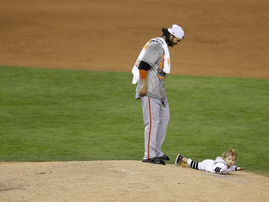 San Francisco Giants' Brandon Crawford walks on the mound after Game 7 of baseball's World Series against the Kansas City Royals, Wednesday, Oct. 29, 2014, in Kansas City, Mo. The Giants won 3-2 to win the series. (AP Photo/Jeff Roberson)