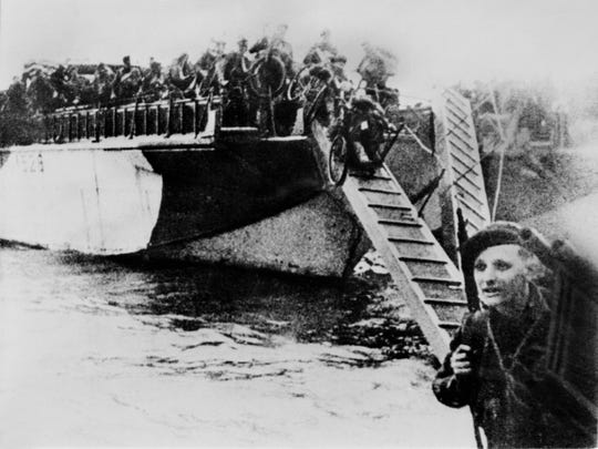 UTAH BEACH, FRANCE:  French commandos equiped with bikes disembark from crafts during D-Day 06 June 1944 after Allied forces stormed the Normandy beaches. D-Day, 06 June 1944 is still one of the world's most gut-wrenching and consequential battles, as the Allied landing in Normandy led to the liberation of France which marked the turning point in the Western theater of World War II.