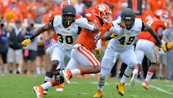 Clemson quarterback Deshaun Watson scrambles out of the pocket avoiding the tackle attempt by Appalachian State's Ronald Blair during the first half Saturday, Sept. 12, 2015,  in Clemson, S.C.