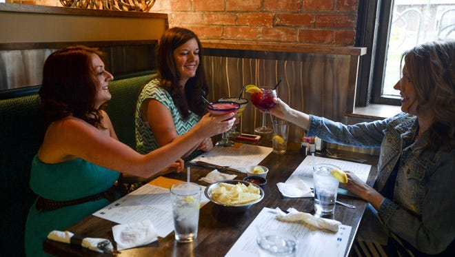 From left, Elizabeth Klopfenstein, Rebekah Klopfenstein and Amanda Wright toast their night out at Blue Agave Grill, a new restaurant in Fort Collins, Sunday, May 18, 2014.