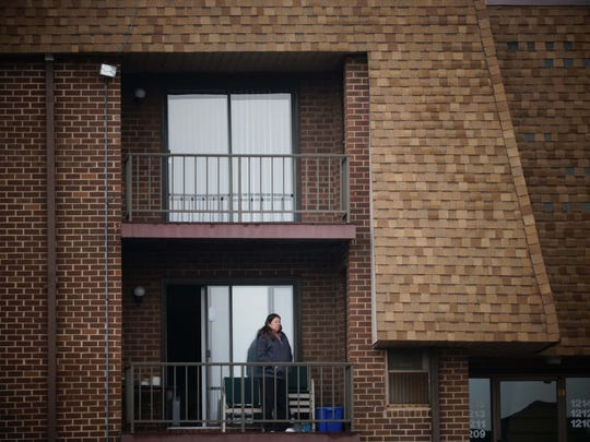 A resident looks out over the parking lot at the Preserve at Deacons Walk apartments, where another attempted abduction happened Monday night.