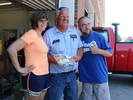 Marlee Fejes, left, and Alex Shrewsbury, right, hand-delivered cookies on behalf of the Ottawa County Board of Developmental Disabilities to those who helped with the torch run last month, such as Ernest Wylie, center, of the Catawba Island Township Fire Department.