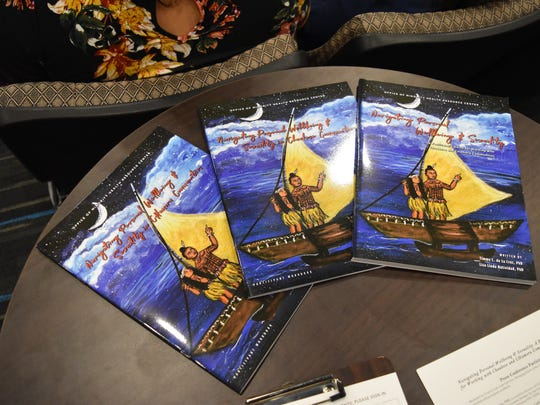 """Copies of """"Navigating Personal Wellbeing & Sexuality: A Facilitator's Guide for Working with Chuukese and CHamoru Communites"""" are displayed on a media table during a press conference for the culture-based curriculum at the Guam Museum on Sept. 19, 2017."""