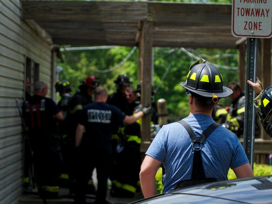 KFD firefighters regroup outside an apartment building in the Meadow Woods complex on Pleasant Ridge Road on Sunday following a kitchen fire that spread into the building's attic.