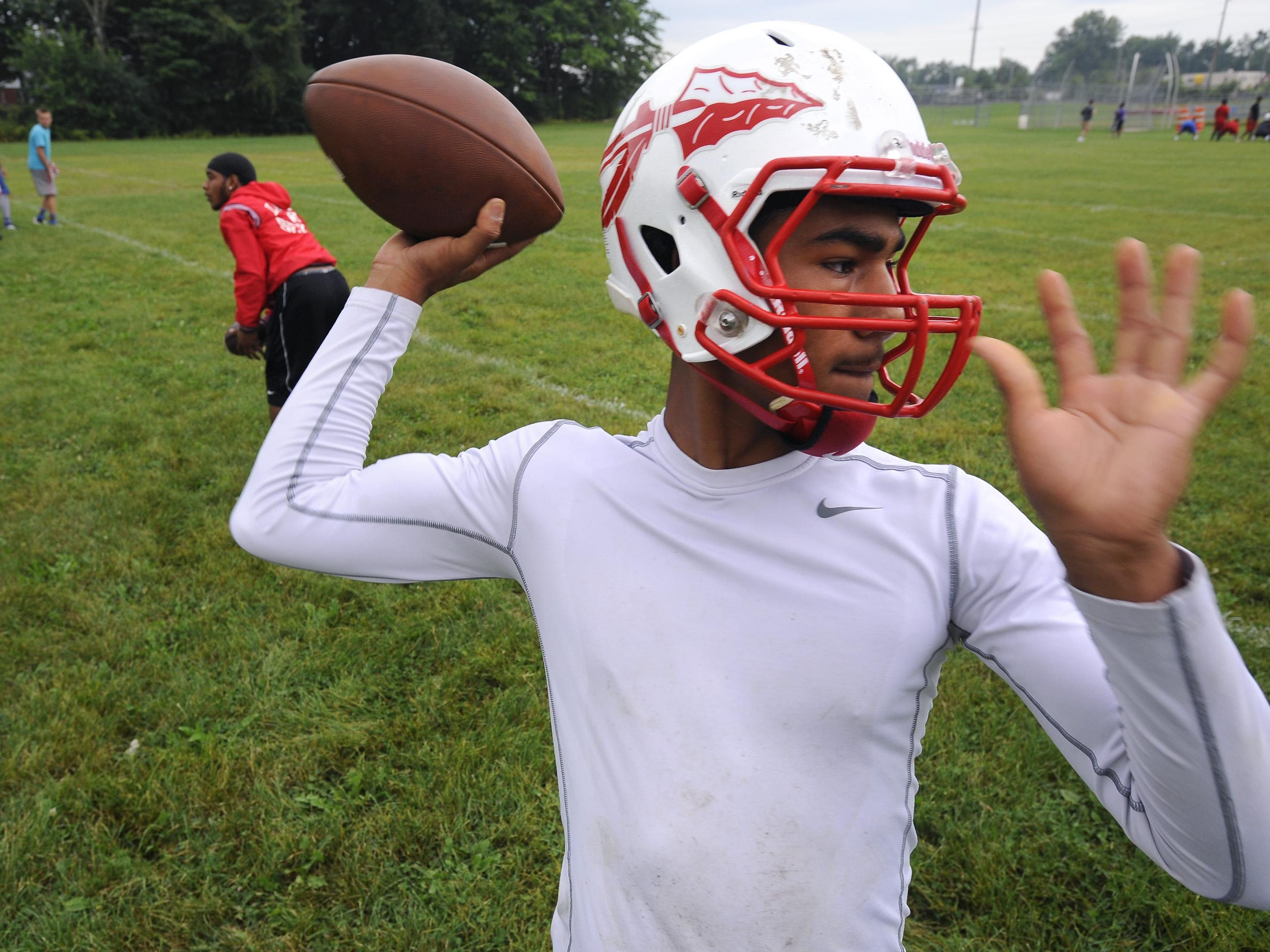 Sexton quarterback Michael Lynn III throws to receivers at the opening of football practice Monday morning.