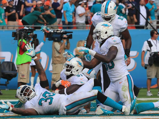 Miami Dolphinssafety Michael Thomas (center) celebrates with strong safety Chris Clemons (30) and defensive end Dion Jordan (95) after his interception of New England Patriots quarterback Tom Brady (not pictured) in the fourth quarter at Sun Life Stadium.