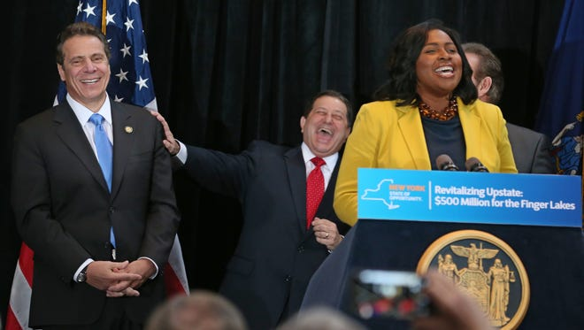 State Assembly Majority Leader Joseph Morelle, center, jokes with Gov. Andrew Cuomo, left, as Rochester Mayor Lovely Warren addresses the packed room at the celebration of the $500 million in economic development grants the state awarded to the Finger Lakes economic development council last week, at the Riverside Convention Center in downtown Rochester Monday, Dec. 14, 2015.