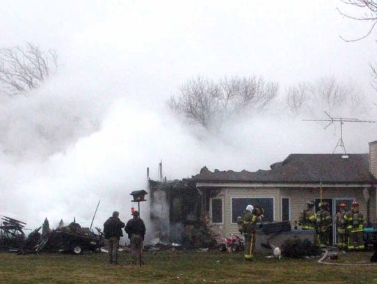 Firefighters work at the scene of a fire at a home