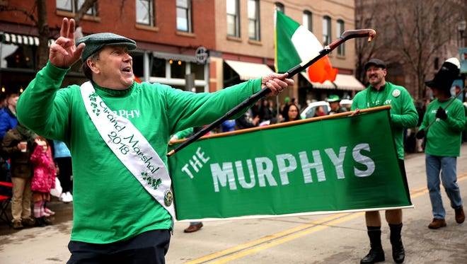 Patrick Murphy, the 2018 Grand Marshal for the St. Patrick's Day Parade, waves to parade-watchers as he walks down Phillip's Avenue in downtown Sioux Falls on Saturday, March 17.