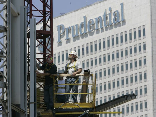 Construction workers are seen on scaffolding on the