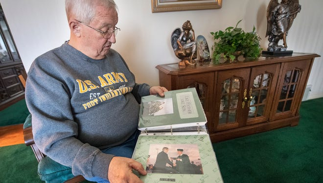 John Knapp looks though an album of photos of his son's short life, with a photo of Jason Knapp's high school graduation in the foreground. The Central York graduate disappeared 20 years ago while attending college in South Carolina.