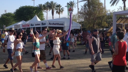 Large groups at the Coachella Valley Music and Arts Festival use pool noodles and other devices to help keep the group together.