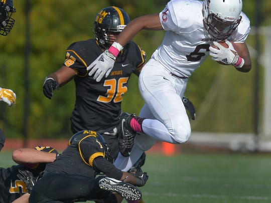 Aquinas' Taylor Riggins, right, breaks the tackle of McQuaid's Noah Williams during a regular season game played at McQuaid Jesuit High School on Saturday, October 10, 2015.