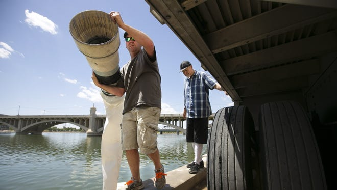 Jason Eldridge of Catfish Express moves a tube from one chamber containing goldfish to another as Johnny Moto of Phoenix looks on. Over a million goldfish and minnows were released into Tempe Town Lake on April 29, 2016. The fish were trucked in from Arkansas to help control mosquitoes and other insects at the lake.
