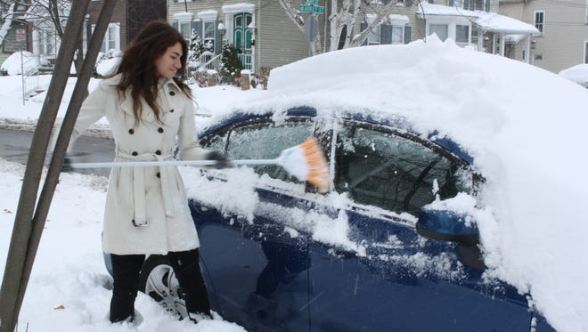 Sarah Rotter, 20, of Binghamton, cleans her car off with a broom Monday morning.