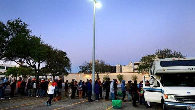 GABE HERNANDEZ/CALLER-TIMES People stand in line to receive a meal and clothes from members of A Body of Christi Street Ministry on Thursday, March 24, 2016, at City Hall in Corpus Christi. There is an initiative underway to encourage groups who feed the homeless outdoors to relocate their ministries to T.C. Ayers Park.