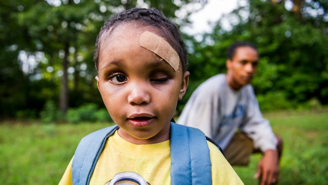In this July 2016 photo, 3-year-old Zachaeus Waters stands with his father, Daquan, outside their home in Fletcher, North Carolina. Zachaeus was found clinging to life beside his fatally wounded and pregnant mother, Candace Pickens, at Ira B. Jones Park in Asheville on May 11, 2016. Pickens' then-boyfriend Nathaniel Dixon is being tried on several charges in a capital murder trial that's expected to last more than a month.
