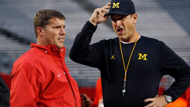 Rutgers head coach Chris Ash, left, and Michigan head coach Jim Harbaugh stand together on the field before an NCAA college football game Saturday, Oct. 8, 2016, in Piscataway, N.J. (AP Photo/Mel Evans)