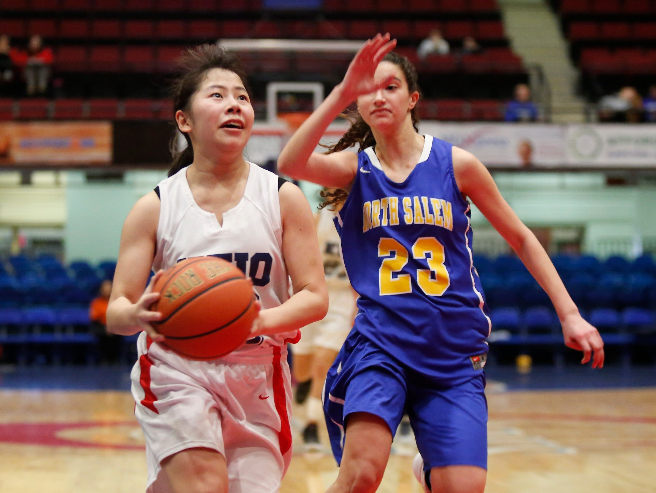 Keio's Ayano Miyauchi (10) dribbles past North Salem's Julia Desanto (23) in the class C semi-final basketball game at the Westchester County Center in White Plains on Saturday, February 27, 2016.