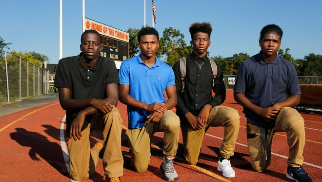 (Left to right:) Pape Coundoul, Da'Shawn Gibson, Dajon Walker and his brother Jajuan Walker kneel on the track at Withrow High School.  During their 2016 season, the four members of the school's football team joined the growing movement of athletes protesting against discrimination during the national anthem. Withrow players have not protested before any games this season.