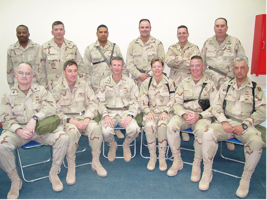 Then-Col. Heidi V. Brown, seated third from right, sits with then-Brig. Gen. Howard B. Bromberg, seated fourth from right, and other air-defense leaders at Camp Virginia, Kuwait, shortly before the start of the Iraq War in 2003.