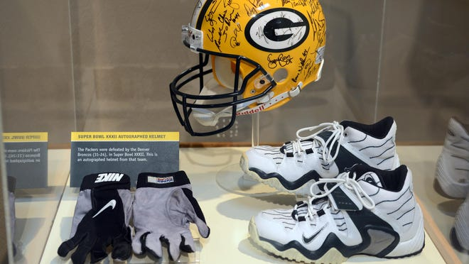 A Green Bay Packers Hall of Fame exhibit of Antonio Freeman's shoes and gloves.