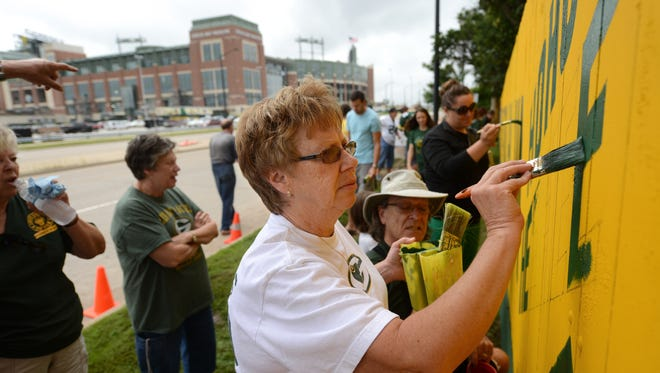 "Mary Janquart of Marinette paints the final letter of the slogan on the original Packers fence Monday at Fred Harrsch's home across the street from Lambeau Field. This year's slogan is ""Welcome to the Frozen Tundra, Ha Ha."""