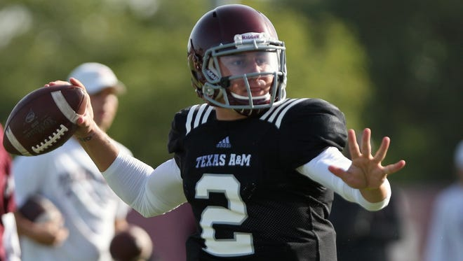 Texas A&M quarterback Johnny Manziel continues to practice with the Aggies as the NCAA investigates allegations he was paid for signing autographs.