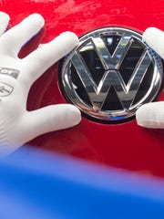 A worker checks the Volkswagen sign on a Golf car during