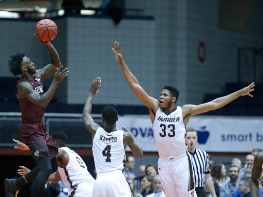 Fordham's Antwoine Anderson, a Bishop Kearney graduate and the 2013 All-Greater Rochester Player of the Year, shoots over St. Bonaventure's Nelson Kaputo and Josh Ayeni in the first half at the Blue Cross Arena at the War Memorial on Saturday.