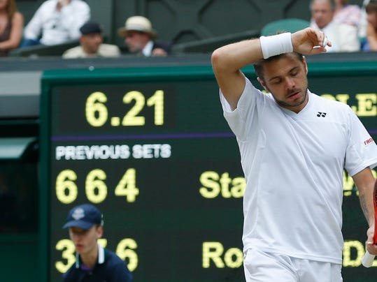 Stan Wawrinka of Switzerland walks along the base line as he plays against Roger Federer of Switzerland during their match at the All England Lawn Tennis Championships in Wimbledon, London, Wednesday, July 2, 2014. (AP Photo/Pavel Golovkin)