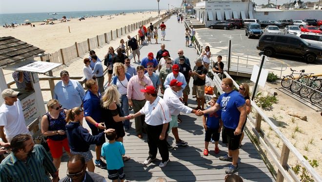 New Jersey Gov. Chris Christie (center left) and Borough of Point Pleasant Beach Mayor Stephen Reid greet people as they walk along the boardwalk to kick off the Memorial Day holiday weekend at the Jersey Shore Friday.