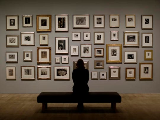 "A Tate member of staff poses in front of a wall of photographs at the press view of ""The Radical Eye: Modernist Photography from the Sir Elton John Collection"" exhibition at the Tate Modern gallery in London, Tuesday, Nov. 8, 2016. British musician Elton John's collection of international modernist photography from the 1920s to 50s includes almost 200 prints and opens to the public on November 10."