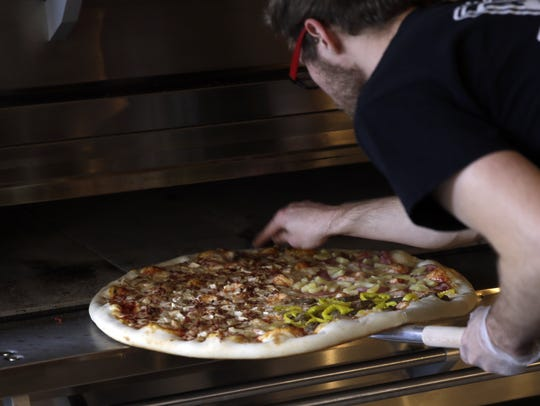 A pizza is checked before it comes out of the oven at Goodfella's Pizza