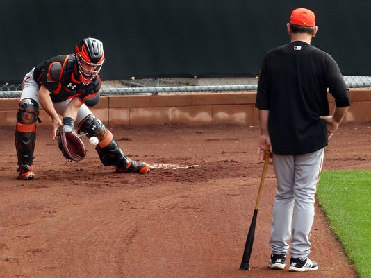 San Francisco Giants manager Bruce Bochy, right, watches catcher Buster Posey during a spring training baseball practice on Thursday, Feb. 15, 2018 in Scottsdale, Ariz. (AP Photo/Ben Margot)