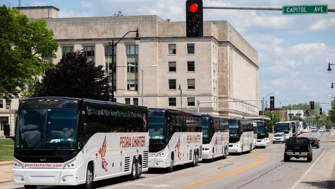 """A rally of motorcoach companies, including Peoria Charter Coach, lineup along Second Street in front of the Illinois State Capitol as they circle the complex during a """"rolling rally"""" to raise awareness of their need for federal assistance as the industry faces financial troubles due to the COVID-19 pandemic, Wednesday, June 17, 2020, in Springfield, Ill. The industry is requesting $15 billion in grants and loans and modifications to Economic Injury Disaster Loan and Paycheck Protection Program to help save the industry."""